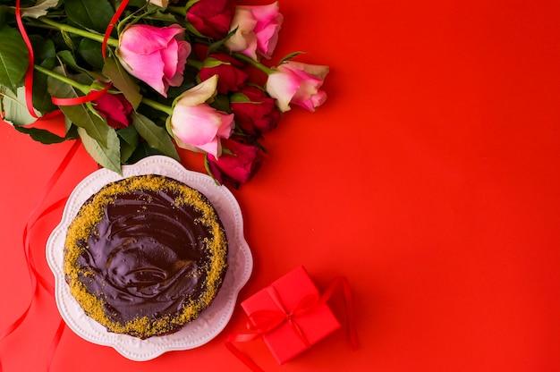 Concept vrouwendag of st. valentijnsdag. verse rozen en geschenkdoos op een rode achtergrond en een chocoladecake. bovenaanzicht kopieer ruimte