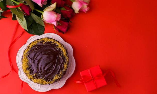 Concept vrouwendag of st. valentijnsdag. verse rozen en geschenkdoos op een rode achtergrond en een chocoladetaart. bovenaanzicht. kopieer ruimte