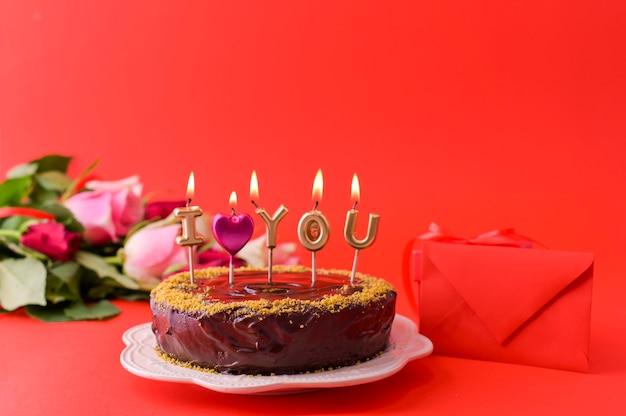 Concept vrouwendag of st. valentijnsdag. verse rozen en geschenkdoos op een rode achtergrond en een chocoladetaart met kaarsen