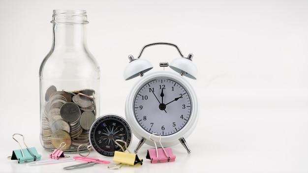 Concept zakelijke financiën en winkelen verkoop munten in pot met witte wekker zakelijke objecten geïsoleerd op een witte achtergrond