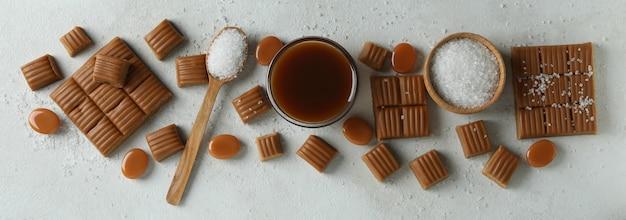 Concept zoet voedsel met karamelstukjes, zout en karamelsaus op witte gestructureerde achtergrond