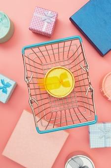 Concept zwarte vrijdag, geschenkdozen met winkelwagentje op roze pastel achtergrond, kopie ruimte, flatlay
