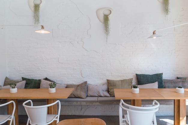 Concepten binnenruimten op witte bakstenen muurtafels en stoelen met bloemendecoratie