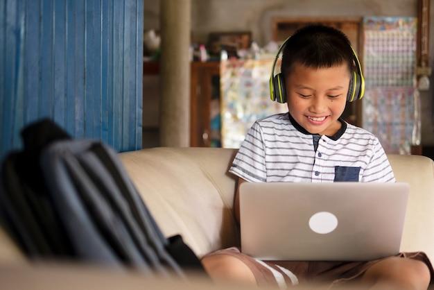 Concepten voor online leren op afstand, afstandsonderwijs en thuisonderwijs. school jongen aziatische preteen jongen in hoofdtelefoon met laptopcomputer op de bank in een rustiek landelijk huis tijdens covid-19 pandemie.