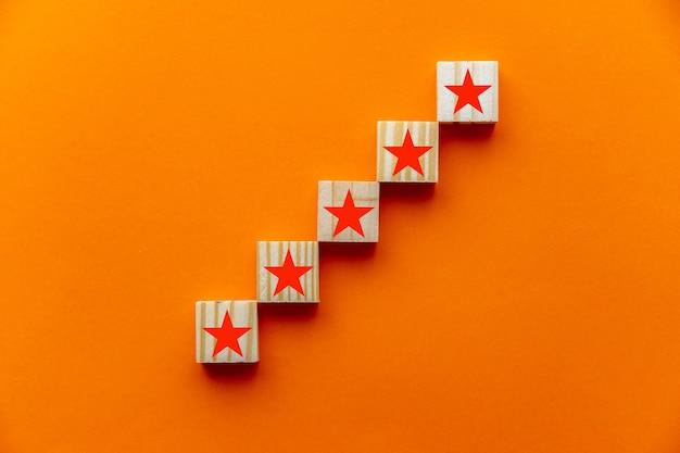 Concepten zoals klantervaring, tevredenheidsonderzoek, evaluatie, beoordeling verhogen en topscore voor uitstekende services. het vijfsterrenteken is afgebeeld op houten blokken op een oranje achtergrond.