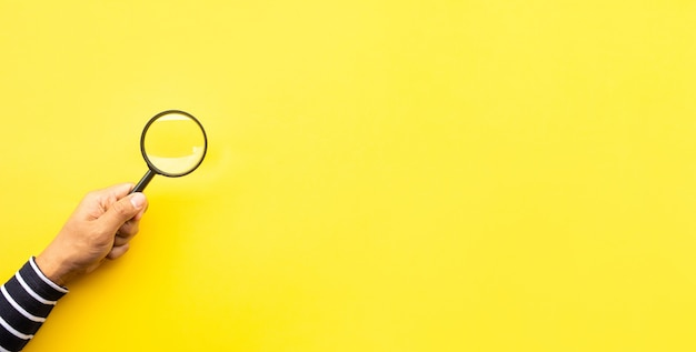 Concepten zoeken met mannenhand met vergrootglas