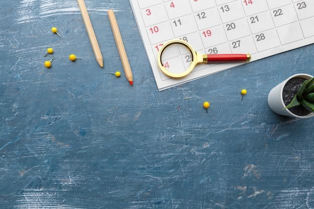 Conceptenbeeld van zaken en vergaderingen. kalender om u te herinneren aan een belangrijke afspraak en vergrootglas