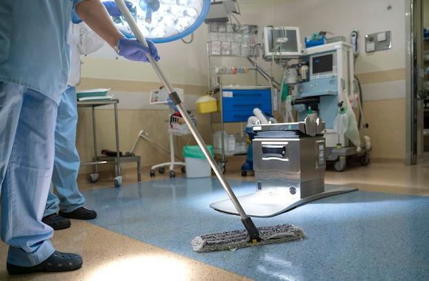 Conceptenfoto van een het ziekenhuisarbeider doen die in verrichtingsruimte schoonmaken