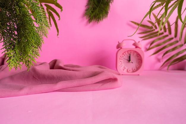 Conceptideeën die het product onder de aandacht brengen. roze achtergrond versierd met, droge bladeren, dennenbladeren, doek en klok.