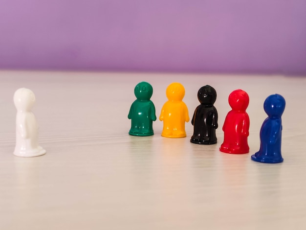 Conceptie - liderschap, leider in een team, diversiteit, spelfiguren of pionnen in een zakelijke situatie. gekleurde fiches van tafelspel in de vorm van kleine mannen