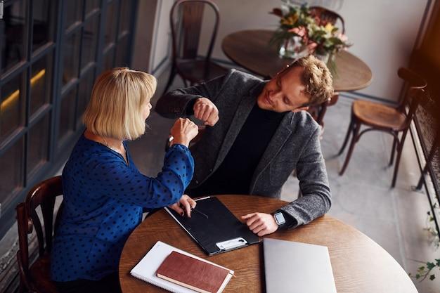 Conceptie van succes. jonge kerel in formele kleding heeft een zakelijk gesprek met oude vrouw in café.