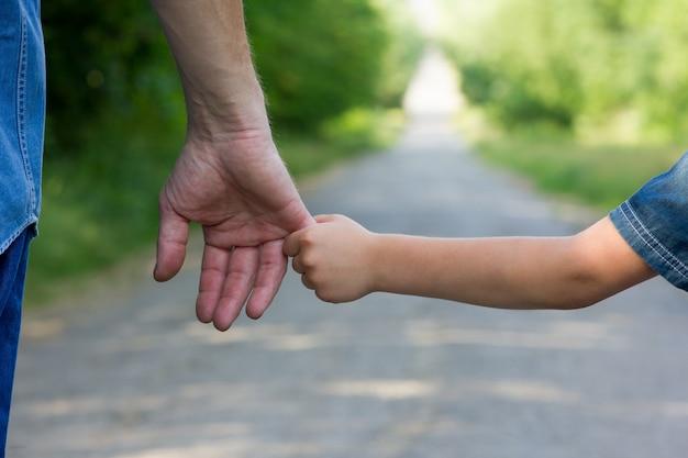 Conceptouder houdt de hand van een klein kind vast en loopt op de weg