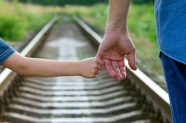 Conceptouder houdt de hand vast van een klein kind en de spoorweg over de toekomst