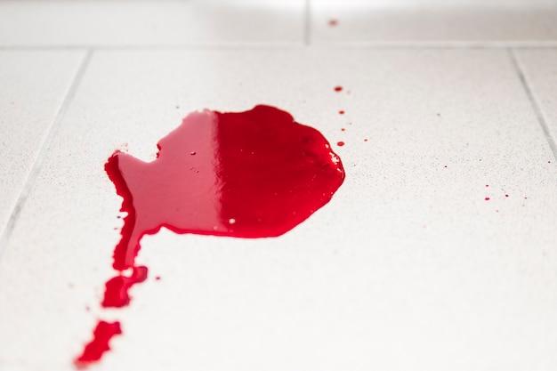 Conceptueel beeld met bloed erop rustend op tegels op de vloer. een plas opgedroogd bloed op de betegelde badkamervloer.