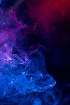 Conceptueel beeld van kleurrijke rode en blauwe kleurenrook die op donkere zwarte achtergrond, halloween-conceptontwerpelement wordt geïsoleerd.