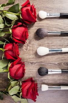 Conceptueel beeld van make-upborstels naast rozen op houten achtergrond
