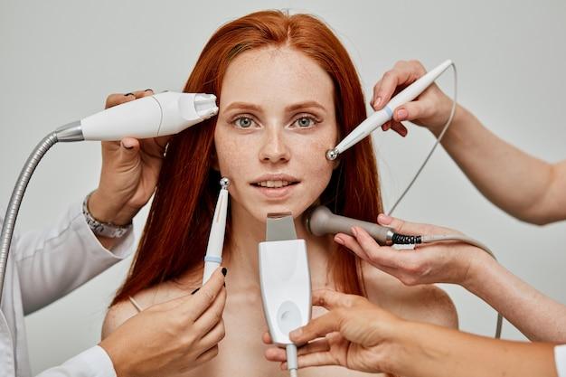 Conceptueel beeld van vrouwelijke emotionele gezicht en schoonheidsspecialisthanden met apparaten