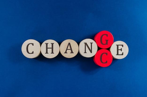 Conceptueel beeld van woordverandering die op houten cirkels wordt gespeld waarbij de tweede tot de laatste cirkel wordt vervangen om het woord kans te spellen.