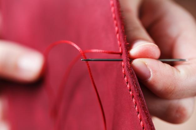 Conceptueel beroep van een leerlooier. de handen van de vrouw sloten zich om de naald en de draad.