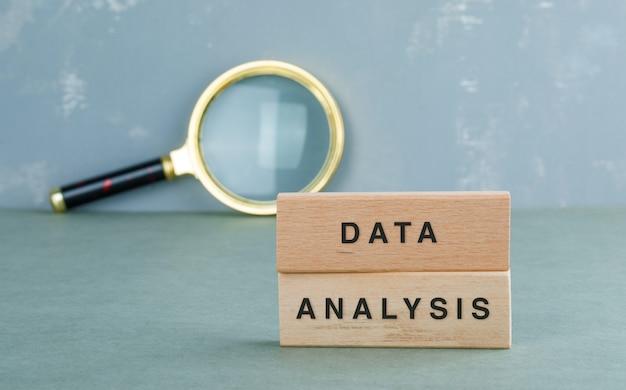 Conceptueel gegevensanalyse met houten blokken, zijaanzicht van het vergrootglas.