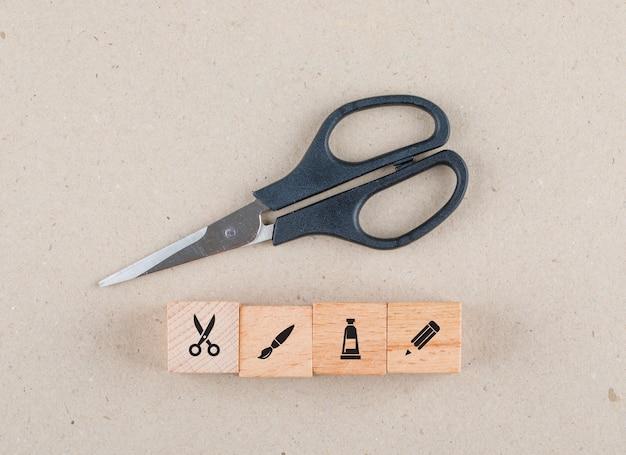 Conceptueel handwerk met houten blokken met pictogrammen, plat schaar leggen.