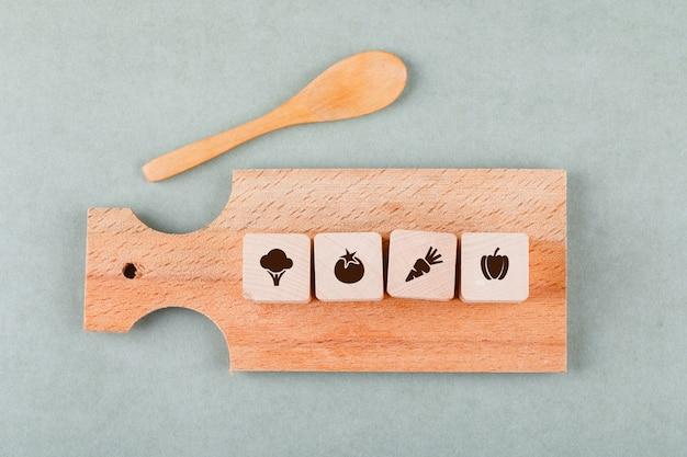 Conceptueel koken met houten blokken met pictogrammen, snijplank, houten lepel bovenaanzicht.