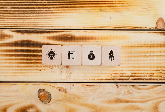 Conceptueel opstarten en bedrijf. met houten blokken met pictogrammen erop op houten tafel plat leggen.