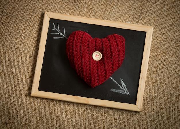 Conceptueel schot van gebreid hart liggend op pijl getekend door krijt