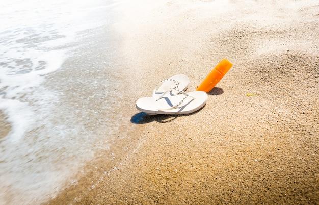 Conceptueel schot van slippers en zonnebrandlotion op zandstrand aan zee