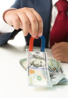 Conceptueel schot van zakenman die magneet vasthoudt en geld van de tafel trekt