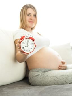Conceptueel schot van zwangere vrouw die op de bank zit en een wekker vasthoudt