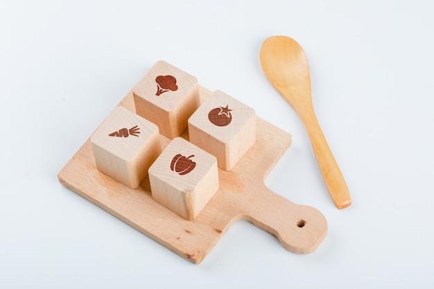 Conceptueel van het koken met houten blokken met pictogrammen op kookbord, houten lepel op witte lijst hoge hoekmening.
