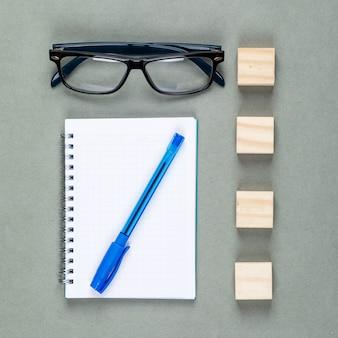 Conceptueel van het maken van aantekeningen met notebook, pen, brillen, houten elementen op grijze achtergrond bovenaanzicht.