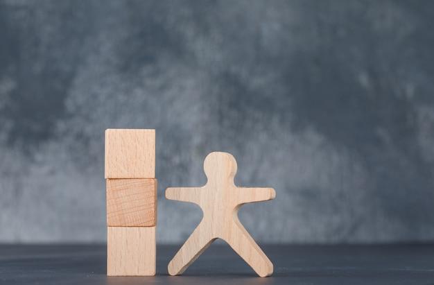 Conceptueel van zaken met houten blokkenkolom met houten menselijk cijfer.