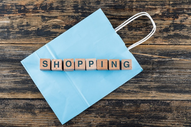 Conceptueel winkelen met houten blokken, boodschappentas op houten tafel plat leggen.