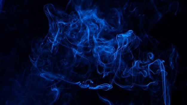 Conceptuele afbeelding van blauwe kleur rook geïsoleerd op donker zwart