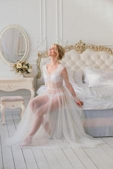 Conceptuele bruiloft. boudoir-jurk, kosten in het interieur studio. wit minimalisme voor de bruid