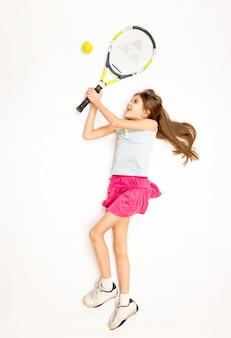 Conceptuele foto van een gelukkig meisje dat op de vloer ligt en een tennisbal raakt met racket