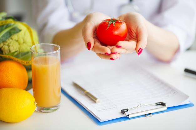 Conceptuele foto van een vrouwelijke voedingsdeskundige with fruits on het bureau