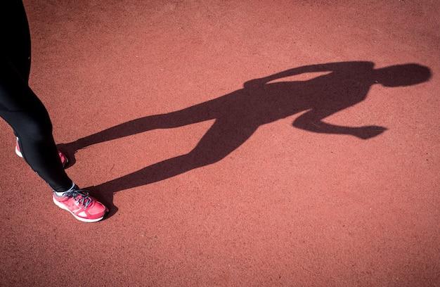 Conceptuele foto van schaduw van lopende vrouw op atletiekbaan