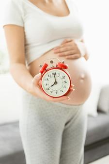 Conceptuele foto van tijd om baby geboren te worden. zwangere vrouw met klokken