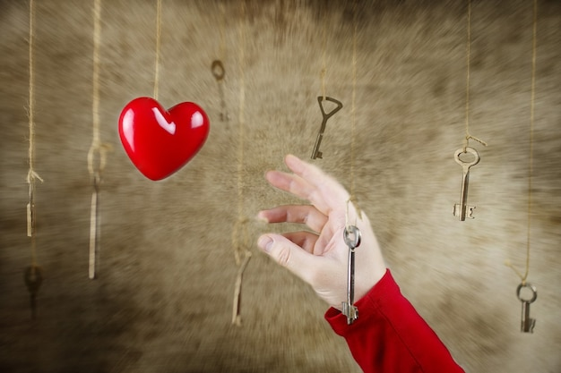 Conceptuele fotohand die zich uitstrekt voor een van de vele oude vintage sleutels die aan draden hangen