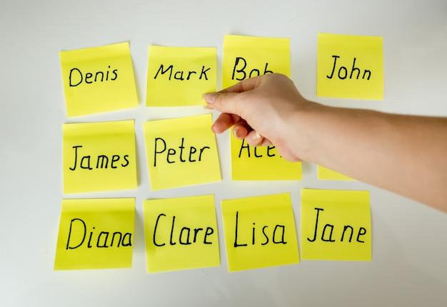 Conceptuele harde keuze van de naam van de baby. handplukpapieren met namen