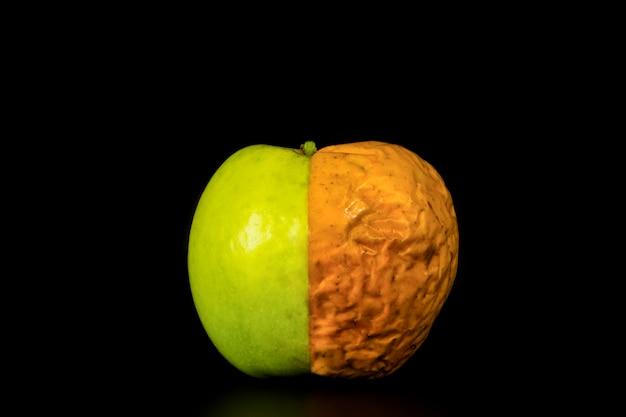 Conceptuele hele appel, jeugd en ouderdom, op zwarte achtergrond
