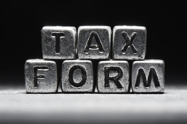 Conceptuele inscriptie belastingformulier op metalen blokjes op een zwart grijze achtergrond close-up geïsoleerd