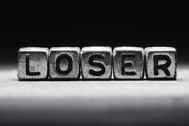 Conceptuele inscriptie verliezer op metalen blokjes op een zwart grijze achtergrond close-up geïsoleerd