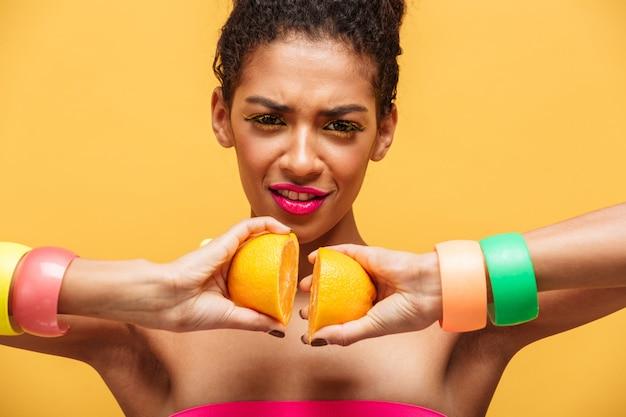 Conceptuele modieuze mulatvrouw met veelkleurige make-up die twee delen van verse sinaasappel opnieuw verbinden die samen, over gele muur opnieuw wordt geïsoleerd