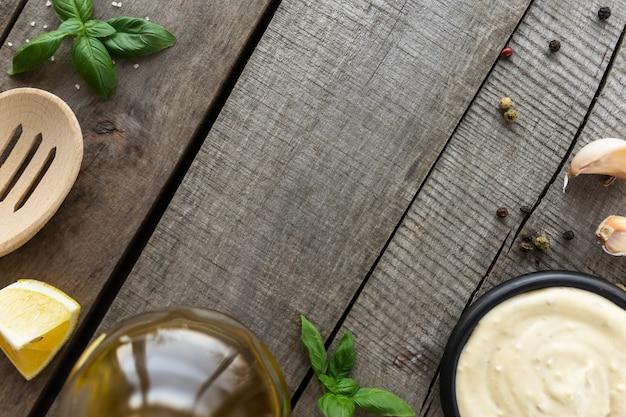 Conceptuele plat leggen. knoflookroomsaus maken of kaassaus koken, eten en kruiden, zelfgemaakte mayonaise, olijfolie in glazen fles op houten tafel.