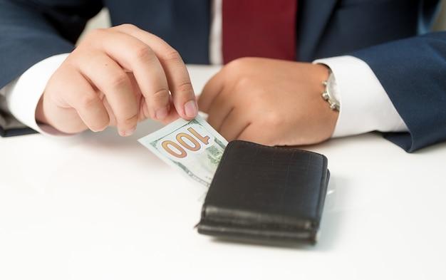Conceptuele zakenman die geld uit de portemonnee haalt