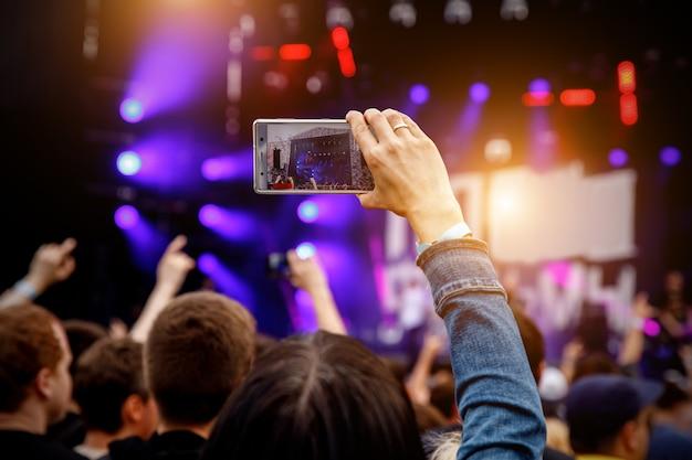 Concert opnemen via smartphone. mobiele telefoon in opgeheven handen